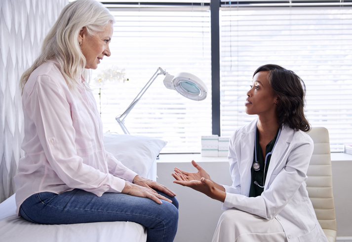 Physician using a combination of medical terminology and simple language to speak to a patient.
