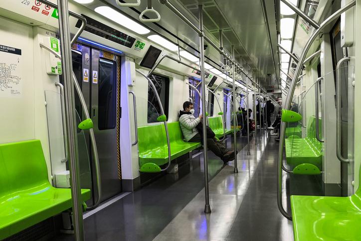 Man on a subway practicing social distancing.