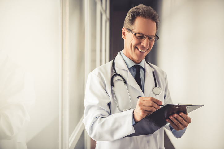 Physician works on writing a letter of recommendation.